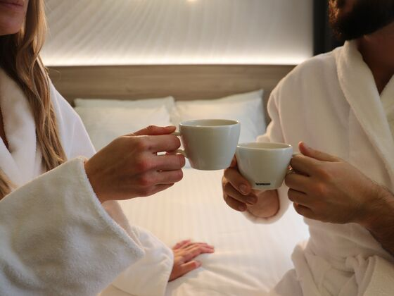 Couple enjoying coffee in bed at Hôtel Château Joliette