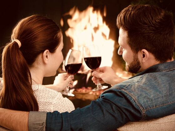 couple with glass of wine in front of the fireplace at Ripplevoce, Hotel & Spa
